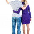 Royalty-Free Stock Photo: Young couple pointing at wal Back view