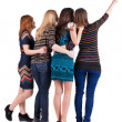 Stock Photo: Back view of group beautiful women pointing at wall.