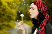Girl blowing on dandelion — Stock Photo