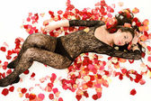 Attractive woman lying on the petals of flowers — Stock Photo