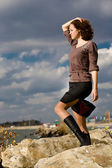 Young attractive woman on the rock coast — Stock Photo