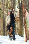 Foto del hombre que sostiene un palo sobre perro saltando — Foto de Stock