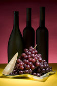 Red grape and wine bottle still life — Stock Photo