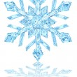 Light blue crystal snowflake on glossy white — Stock Photo