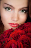 Woman with a bouquet of red roses — Foto de Stock