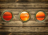 Three portholes with view at the sunrise — Stock Photo