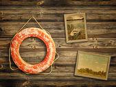 Bouée de sauvetage et de vieux voyage photos à fond en bois — Photo