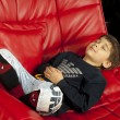 Kid on a red leather sofa — Stok fotoğraf
