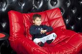 Kid sur un canapé en cuir rouge — Photo