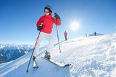 Meisjes zitten en lachend in sneeuw op zonnige dag - winterpret — Stockfoto