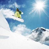 Snowboarder at jump inhigh mountains — Photo