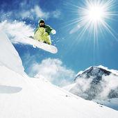 Snowboardåkare på hoppa inhigh berg — Stockfoto