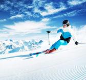 Sciatore in montagne, piste preparate e giornata di sole — Foto Stock