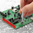 A hand hand with tweezers holding a electronic circuit board on — Stock Photo