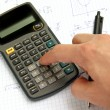 Scientific calculator on notebook paper and a hand — Stock Photo