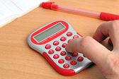 Red calculator and a hand — Stock Photo