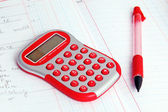 Red calculator on a notebook and red pencil — Stok fotoğraf