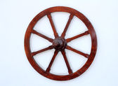 Old wooden wheel on wall — Stock Photo