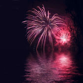 Fireworks reflecting in water as background — Stock Photo