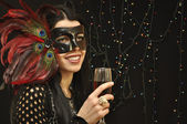 Lady in fancy mask with a glass of wine on black background — Stock Photo