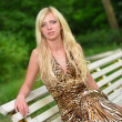 Foto Stock: Portrait of a pretty woman in a Park on a bench