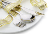 Spoon, fork and a knife tied up celebratory ribbon — Stock Photo
