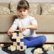 The little girl plays wooden toy cubes — Stock Photo