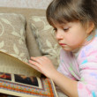 The little girl reads the book lying on a sofa — Stockfoto