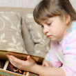 The little girl reads the book lying on a sofa — Stock Photo