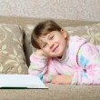 The little girl reads the book lying on a sofa — Stock Photo #9407516