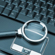 Magnifying glass and a laptop — Stock Photo