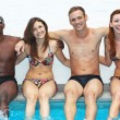 Multi-ethnic friends sitting on side of pool — Stockfoto