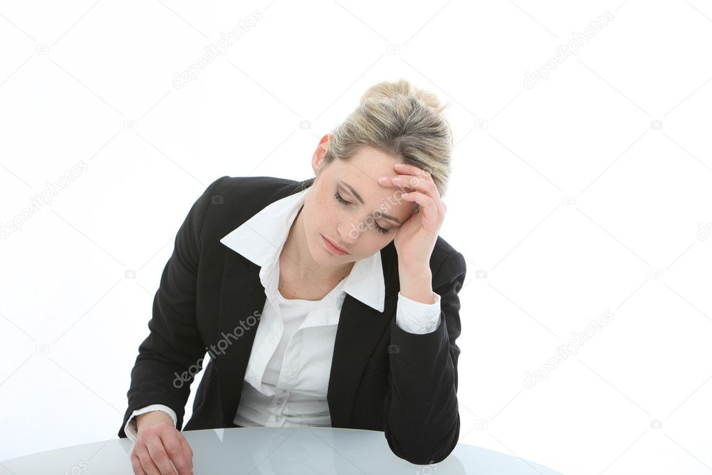 Dejected despondent businesswoman sitting at a table whith her eyes downcast and her head in her hand — Stock Photo #10286257