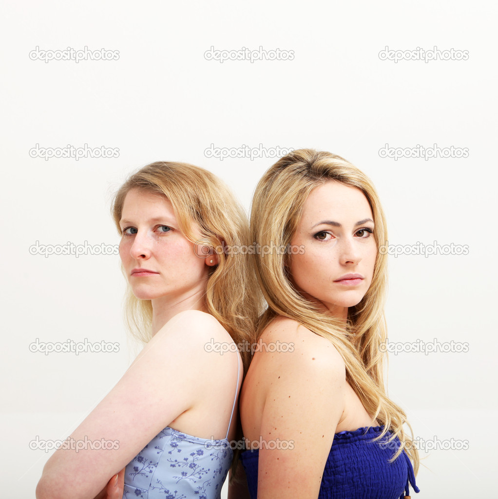 Two serious women standing back to back on white background — Stock Photo #10707854