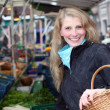 Woman buys vegetables at the market with a basket - Lizenzfreies Foto