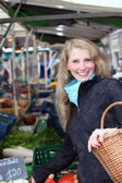 Woman buys vegetables at the market with a basket — Stock Photo