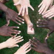 Circle of hands with young from different nations - Stock Photo