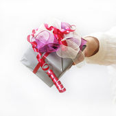 Woman shows nice gift with bow — Stock Photo