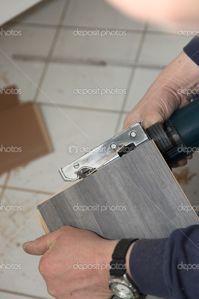 Cropped view of the hands of a handyman trimming tiles with a cutter above a tiled floor in a DIY concept — Stock Photo #9747090