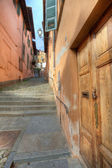 Wooden door and small paved street in Saluzzo. — Stockfoto