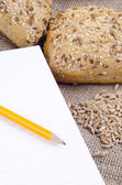 Multigrain roll and a booklet for notes — Stock Photo