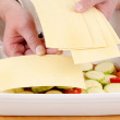 Female chef fills lasagne dish with prepared lasagne sheets — Stock Photo #10598977