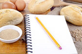 French roll and a booklet for notes — Stock Photo