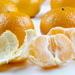 Stock Photo: One open organic mandarin and some in background