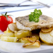 Haddock fillet on a plate with grilled potato and garlic - Stock Photo