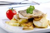 Haddock fillet on a plate with grilled potato and garlic — Stock Photo
