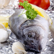 Sea ​​bass on an aluminum foil with vegetables - Stock Photo