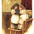 Two little girls have a look at picture — Stock Photo