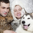 Young couple with a malamute dog — Stock Photo