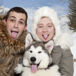 Young couple with a malamute puppy - Stock Photo